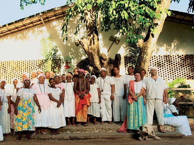 Outside the barracão at Ilê Axé Opô Aganjú, in Lauro de Freitas, with the double-headed axe of Xangó above the door. The pai-de-Santo, Balbino Daniel de Paula, is at the centre of the picture wearing a red and yellow cloth and a string of blue beads.
