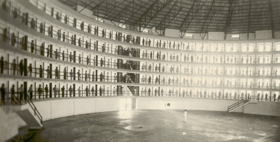 Prisoners stand at attention outside their cells in a rotunda c.1940.